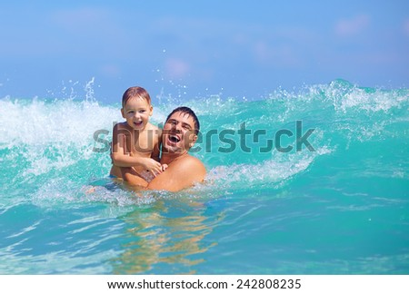 happy father and son having fun in water waves - stock photo