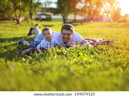 Happy father and son having fun lying on the grass in summer sunny day. Sunlight on the sunset - stock photo