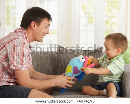 Happy father and son having fun playing on couch at home. - stock photo