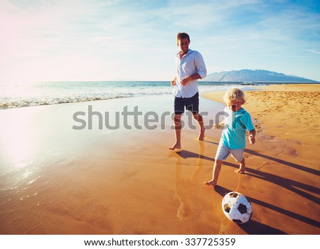 Happy Father and Son Having Fun Playing Soccer on the Beach at Sunset - stock photo