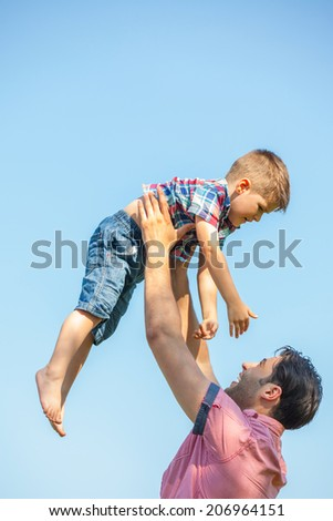 happy  father and son having fun throws up in the air child, family, travel, vacation, father's day - concept