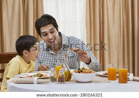 Happy father and son having pizza at restaurant - stock photo