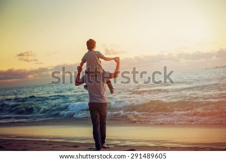 Happy father and son having quality family time on the beach on sunset on summer holidays. Lifestyle, vacation, happiness, joy concept - stock photo