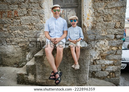 Happy father and son having rest outdoors in city on beautiful summer day - stock photo