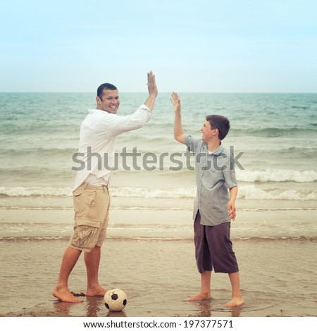 Happy father and son high-fiving on the beach