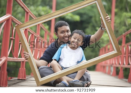 Happy father and son holding a frame on a bridge - stock photo