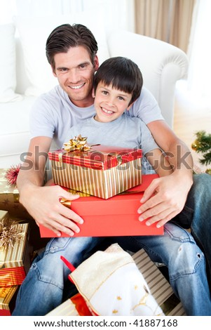 Happy father and son holding Christmas gifts in the living-room