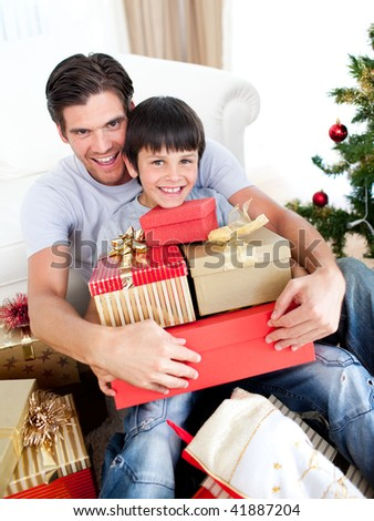 Happy father and son holding Christmas presents at home