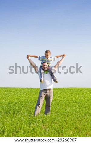 Happy father and son in a wheat field - stock photo