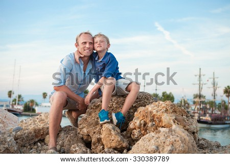 Happy father and son in sunset sea harbor - stock photo