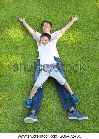 happy father and son lying on a meadow together - stock photo