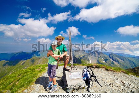 """Happy father and son on the Buteanu peak in Romanian Carpathians, the inscriptions reads """"Peak Buteanu, 2507 m"""" - stock photo"""
