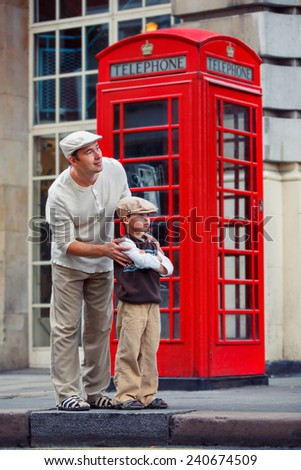 Happy father and son outdoors in city by red phone booth - stock photo