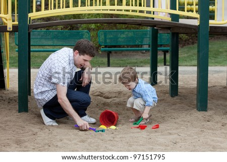 Happy Father And Son Playing At Playground In Sand With Toys.