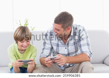 Happy father and son playing games on cell phone at home - stock photo
