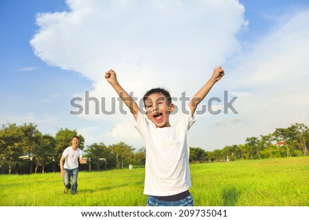 happy father and son playing in meadow - stock photo