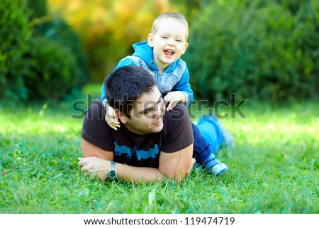 happy father and son playing on green field