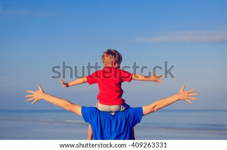 happy father and son playing on sea - stock photo