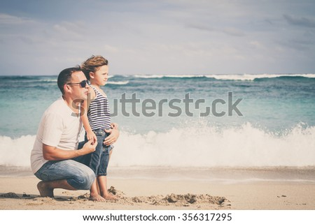 Happy father and son playing on the beach at the day time. Concept of friendly family. - stock photo