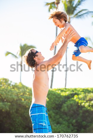 Happy father and son playing on tropical beach, carefree happy fun smiling lifestyle - stock photo