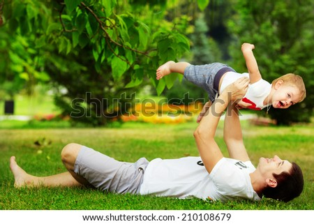 Happy father and son playing together having fun in the green summer park on a warm sunny day. Family and love concept. - stock photo