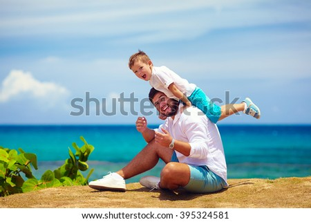 happy father and son playing together near the seaside