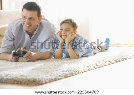 Happy father and son playing video game on floor at home - stock photo