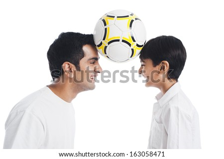 Happy father and son playing with soccer ball - stock photo