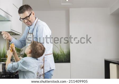 Happy father and son preparing spaghetti in kitchen - stock photo