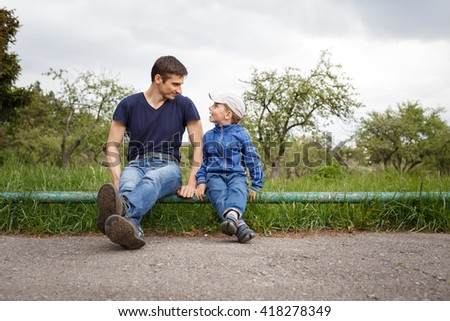 Happy father and son sitting in the park. Smiling young man spending time together with his son.  - stock photo