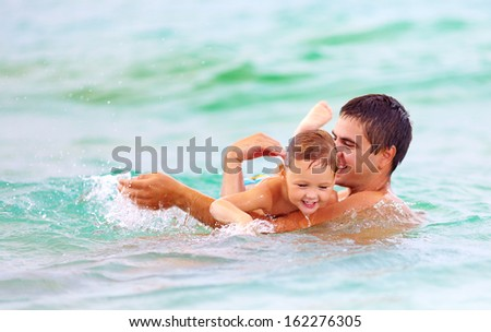 happy father and son swimming in sea water - stock photo