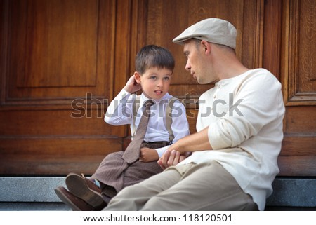 Happy father and son talking and having rest outdoors in city  in city on beautiful summer day - stock photo