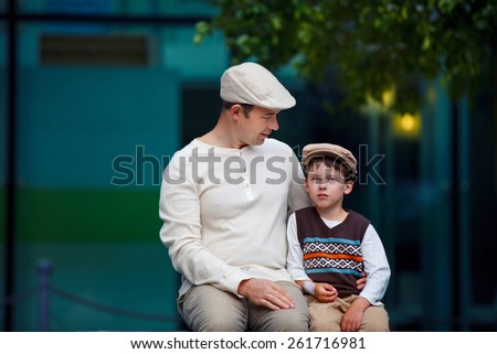 Happy father and son talking and having rest outdoors in city on beautiful summer day - stock photo
