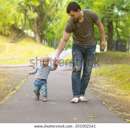 Happy father and son walking in summer park - stock photo