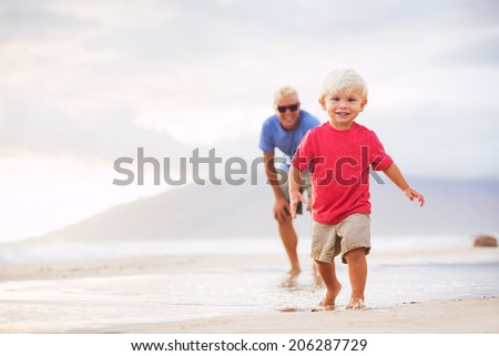 Happy father and son walking on the beach at sunset - stock photo