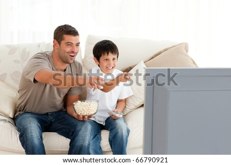 Happy father and son watching television while eating pop corn at home - stock photo
