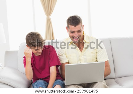 Happy father and son with laptop sitting on sofa at home - stock photo