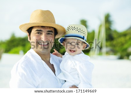 Happy father and son with panama hats on the beach - stock photo