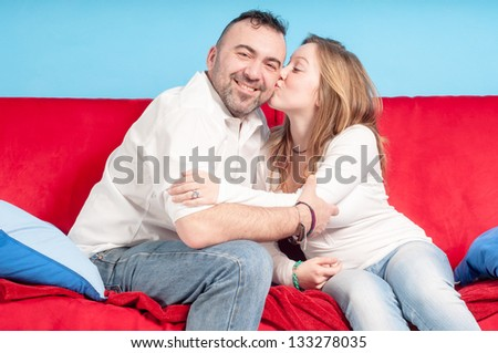 happy father and teenage daughter on the couch in the living room