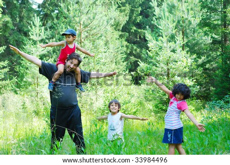 Happy father and three children in nature - stock photo