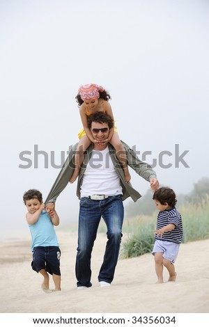Happy father and three kids on the beach - stock photo