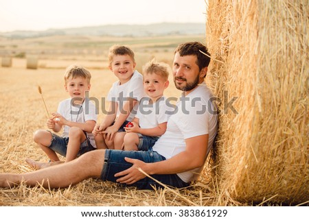 Happy father and three sons in summer in a field of wheat - stock photo