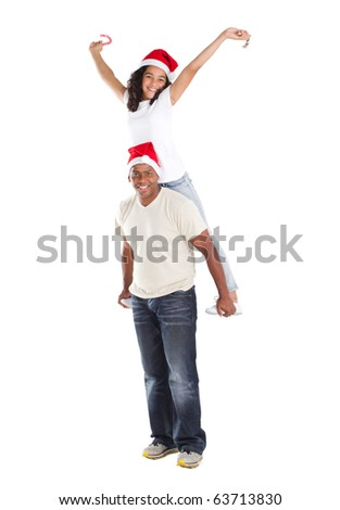 happy father carring daughter on his back wearing Christmas hat and holding candy cane - stock photo