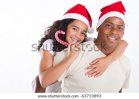 happy father carrying daughter on his back with Christmas hat - stock photo