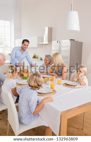 Happy father cutting the turkey for thanksgiving - stock photo