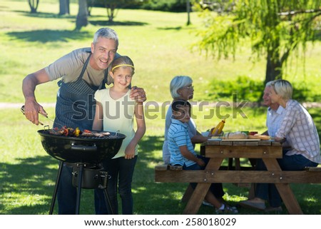 Happy father doing barbecue with his daughter on a sunny day - stock photo