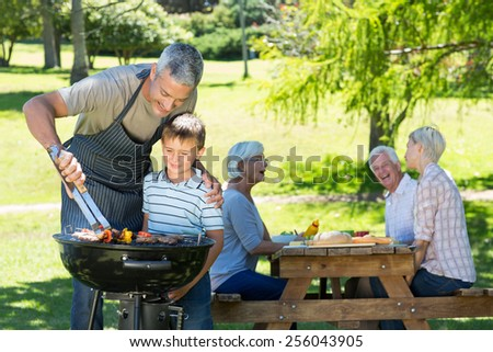 Happy father doing barbecue with his son on a sunny day - stock photo