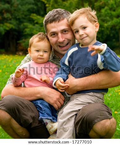 Happy father embracing his children - stock photo