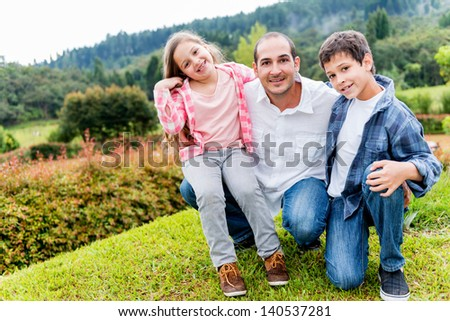 Happy father enjoying with his kids outdoors and smiling - stock photo