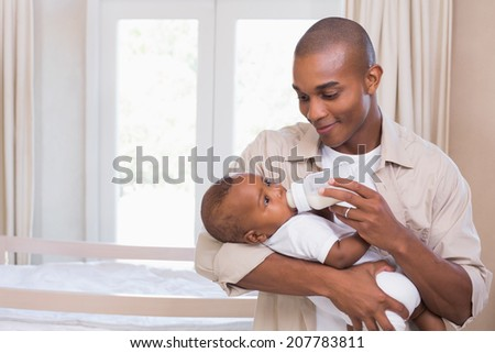 Happy father feeding his baby boy a bottle at home in the bedroom - stock photo